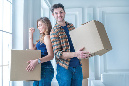 Mudarse a una nueva vida. Una chica y un chico celebración de cajas para mover las manos y sonriendo a la cámara mientras una pareja en el amor de pie junto a la ventana entre cajas