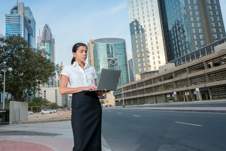 formal attire: Work outside the office. Successful businesswoman standing in the street in formal attire and holding a laptop in hand. Arab businessman working on laptop in among the skyscrapers in Dubai Stock Photo