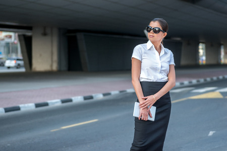 attire: Expectation of success. Confident arabic businesswoman standing in the street in formal attire. Businessman standing near skyscrapers in Dubai downtown in sunglasses waiting for a taxi Stock Photo