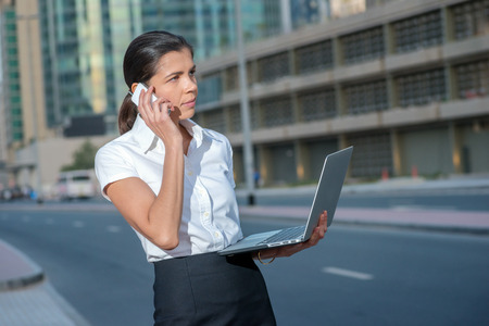 working attire: Business call. Successful businesswoman standing in the street in formal attire holding a laptop while talking on cell phone. Arab businessman working on laptop in among the skyscrapers in Dubai
