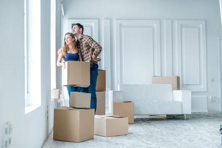 Nieuw leven. Paar in liefde in beweging en houden een doos in zijn handen en kijken naar de camera terwijl een jonge en mooie paar in liefde zittend op de bank in een leeg appartement onder dozen Stockfoto