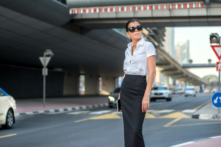 formal attire: Arab business and success. Confident arabic businesswoman standing in the street in formal attire. Businessman standing near skyscrapers in Dubai downtown in sunglasses waiting for a taxi Stock Photo