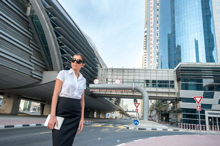attire: New opportunities. Successful arabic businesswoman standing in the street in formal attire. Businessman standing near skyscrapers in Dubai downtown in sunglasses holding a tablet