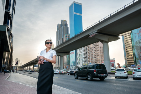 Business in the big city. Successful arabic businesswoman standing in the street in formal attire. Businessman standing near skyscrapers in Dubai downtown in sunglasses holding a tablet