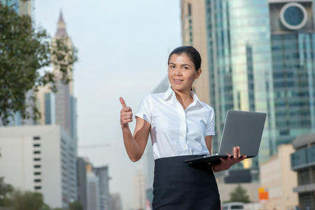 Best work. Successful businesswoman standing in the street in formal attire holding a laptop in his hands and showing thumb up. Arab businessman working on laptop in among the skyscrapers in Dubai Stock Photo