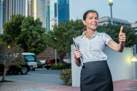 formal attire: Success. Confident businesswoman standing on a street in formal attire holding a laptop and showing thumb up. Arab businessman working on laptop in among the skyscrapers in Dubai