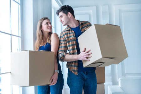 moving: Moving to a new life. A girl and a guy holding boxes for moving the hands and smiling at the camera while a couple in love standing at the window among boxes Stock Photo
