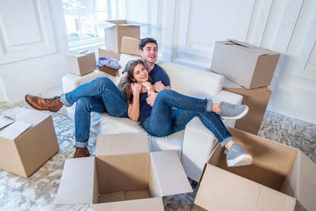 Moving home and repair of a new life. Couple in love pulls things out of boxes for moving while man and woman sitting among the boxes in an empty apartment Stock Photo