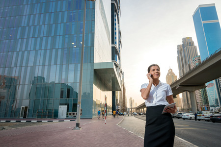 formal attire: Transaction over the phone. Successful businesswoman standing in the street in formal attire. Businessman standing near skyscrapers in downtown in talking on cell phone Stock Photo