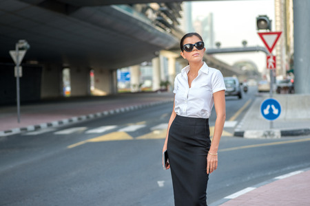 formal attire: Arab business and success. Confident arabic businesswoman standing in the street in formal attire. Businessman standing near skyscrapers in Dubai downtown