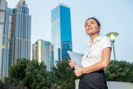 formal attire: Business and woman. Confident businesswoman standing on a street in formal attire holding a laptop and looking forward to. Arab businessman working on laptop in among the skyscrapers in Dubai