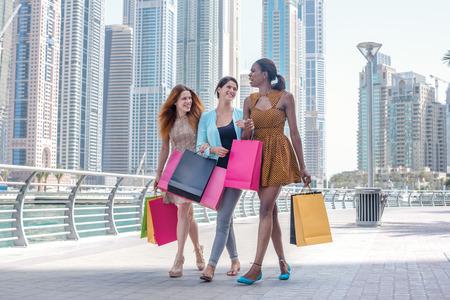 Девушки весело вместе по магазинам. Красивая девушка в платье, холдинг сумок в руках на набережной среди небоскребов во время прогулки по улице с сумками