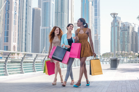 Girls having fun together shopping. Beautiful girl in dress holding shopping bags in their hands on the embankment among the skyscrapers while walking down the street with shopping bags Standard-Bild