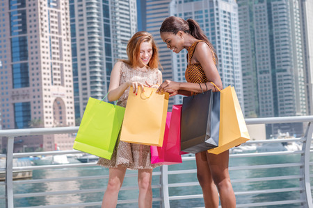 look inside: Joint purchases. Two girl friends in dresses holding shopping bags in their hands on the promenade is to look inside shopping bags