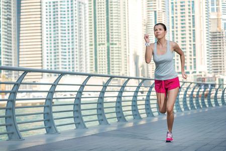 Atleet loopt en maakt de training. Athletic vrouw in sportkleding doen sport oefeningen en warm-up aan de waterkant in Dubai