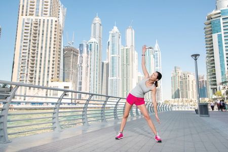 Stretching and sports training. Athletic woman in sportswear doing sport exercises and warm-up on the waterfront in Dubai.