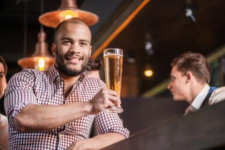 Zelfverzekerde man bier drinken aan de bar. De mens houdt glas bier in zijn hand Stockfoto