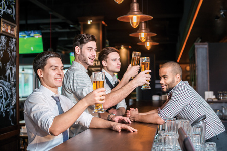 drinks after work: Activities of real men in a bar with beer. Three other men drinking beer and having fun together in the bar until the bartender looks at them Stock Photo