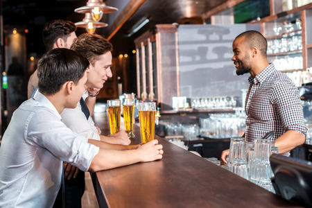 drinks after work: Three friends sitting at the bar and keep the beer. Four friends men drinking beer and having fun together in the bar Stock Photo