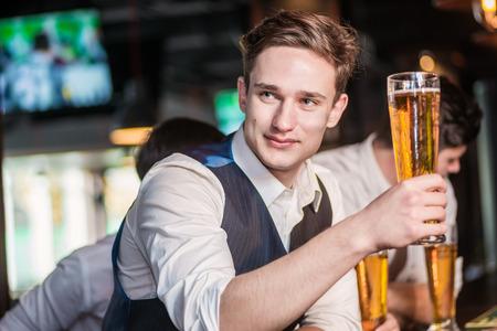 Zekere mens bier drinken aan de bar. De mens houdt glas bier in zijn hand