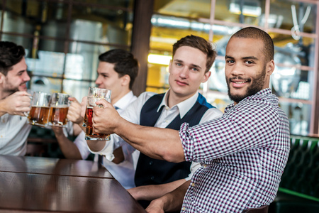 drinks after work: Four businessmen friends drink beer and spend time together in a bar. Confident businessmen having fun with friends at the bar with a beer at the table Stock Photo
