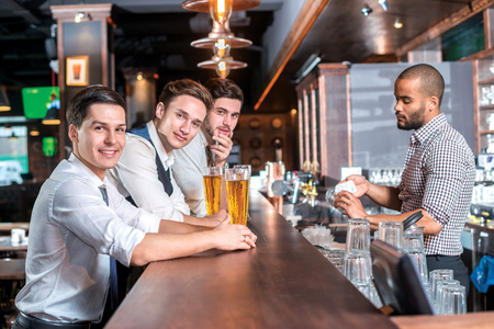 drinks after work: Three friends sitting at the bar and keep the beer. Four friends men drinking beer and having fun together in the bar and look at the camera Stock Photo