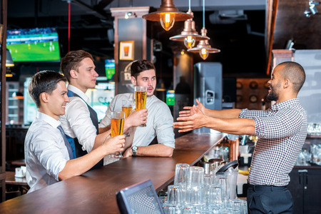 drinks after work: Keep your beer. Four friends drinking beer and having fun together in the bar