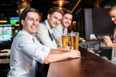 drinks after work: cheerful evening for men. Four friends men drinking beer and having fun together in the bar and look at the camera