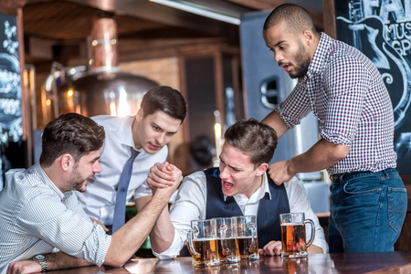 beer after work: Four friends compete at the hands of drink beer and spend time together, laughing at the bar. Confident businessmen having fun with friends at the bar with a beer at the table