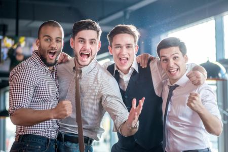 jovenes tomando alcohol: Ventiladores alegres viendo la televisi�n y el f�tbol deleite. Cuatro hombres de �xito gritan y se regocijan encuentro de f�tbol. Amigos que se divierten juntos viendo la televisi�n Foto de archivo