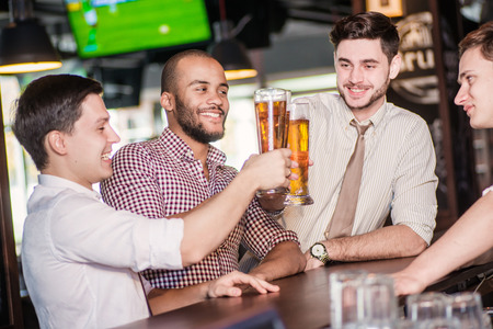 communicates: Beer and football in the bar. Three other men drinking beer and having fun together in the bar until the bartender communicates with them
