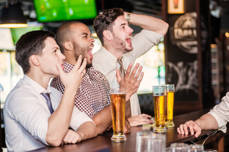 horizontal bar: Men fans watching football on TV and drink beer. Three other men drinking beer and having fun together in the bar until the bartender communicates with them