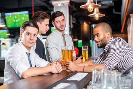 after to work: Rel�jese despu�s del trabajo. Cuatro amigos bebiendo cerveza y se divierten juntos en el bar Foto de archivo