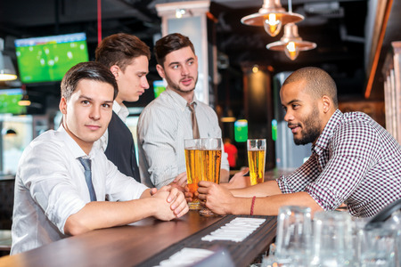 beer after work: Relax after work. Four friends drinking beer and having fun together in the bar Stock Photo