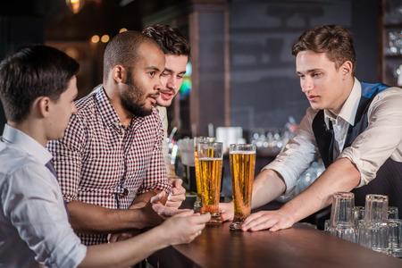jovenes tomando alcohol: Hombres seguros bebiendo cerveza en la barra. Los hombres gritan y se regocijan en reuniones y beben cerveza. El camarero sirve a clientes Foto de archivo