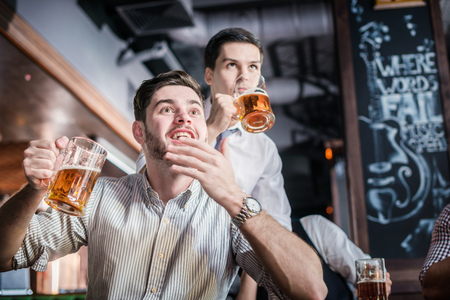 beer after work: Two successful businessmen drink beer and rejoice and shout together watching TV at the bar. Confident business people having fun with friends at the bar with a beer watching football on TV