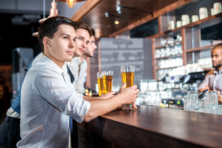 beer after work: Drinking alcohol in a bar. Three friends men drinking beer and having fun together in the bar and look at the camera