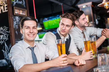 beer after work: Relax in the bar after a hard work. Four friends men drinking beer and having fun together in the bar and look at the camera Stock Photo