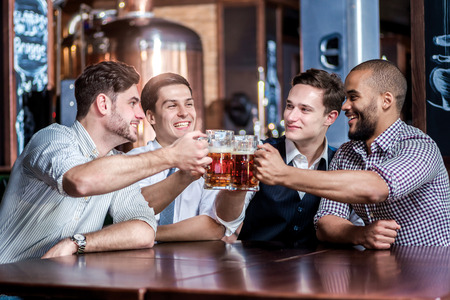 Vier zakenlieden bier drinken en verheugen zich samen aan de bar. Vertrouwen in mensen uit het bedrijfsleven plezier met vrienden aan de bar met een biertje.