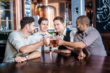 drinks after work: Four businessmen friends drink beer and spend time together in a bar. Confident business people having fun with friends at the bar with a beer at the table