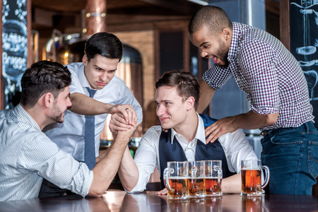 drinks after work: Four friends struggle on their hands drink beer and spend time together, laughing at the bar. Confident businessmen having fun with friends at the bar with a beer at the table