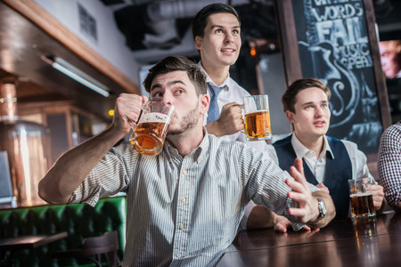 Three successful businessmen drink beer and rejoice and shout together watching TV at the bar. Confident business people having fun with friends at the bar with a beer watching football on TV