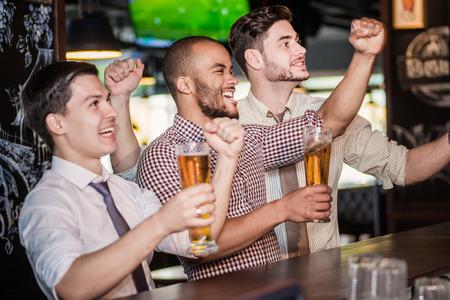 Men fans zwaaien met hun handen en het kijken naar voetbal op tv en te drinken bier. Drie andere mannen het drinken van bier en plezier samen in de bar terwijl er een voetbalwedstrijd op tv Stockfoto