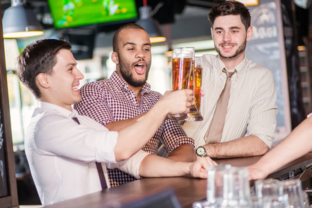 communicates: Men drink beer and enjoy the stay. Three other men drinking beer and having fun together in the bar until the bartender communicates with them