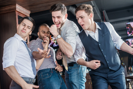 Pick the best of friends. Four men shout and rejoice meeting. Friends having fun together