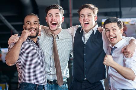 Zelfverzekerd fans TV en verrukking voetbal kijken. Vier succesvolle mannen schreeuwen en zich verheugen voetbal vergadering. Vrienden plezier samen tv kijken Stockfoto