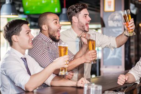 Mannen fans schreeuwen en het kijken naar voetbal op tv en drinken bier. Drie andere mannen het drinken van bier en plezier samen in de bar tot de barman die zich dichtbij het rek