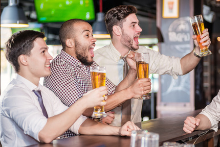 Men fans screaming and watching football on TV and drink beer. Three other men drinking beer and having fun together in the bar until the bartender standing near the rack Standard-Bild