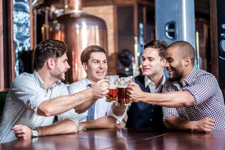 Vier zakenlieden bier drinken en verheugen zich samen aan de bar. Succesvolle zakenlieden vrienden plezier samen in de bar met een biertje.