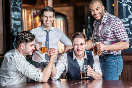 drinks after work: Four friends having fun and drinking beer and spend time together, laughing at the bar. Confident businessmen having fun with friends at the bar with a beer at the table Stock Photo